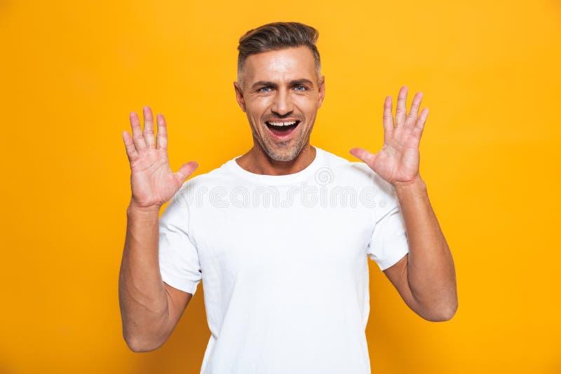 Hübsche glückliche aufgeregte Mannaufstellung lokalisiert über gelbem Wandhintergrund stockbild