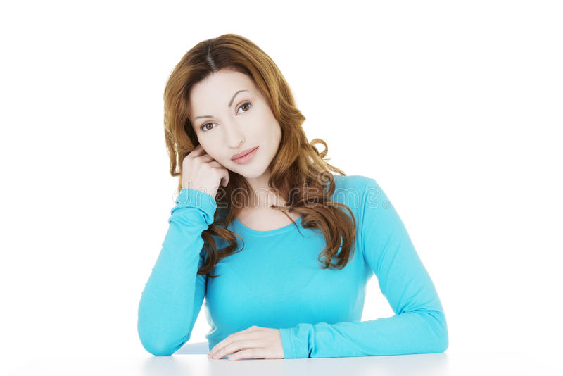 Hübsche, glückliche Frau in der zufälligen Kleidung, die am Schreibtisch sitzt lizenzfreie stockfotografie