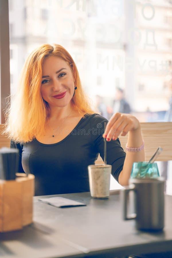 Hübsche glückliche redheaded kaukasische Frau im schwarzen Hemdgetränktasse kaffee im modernen Café allein stockbilder