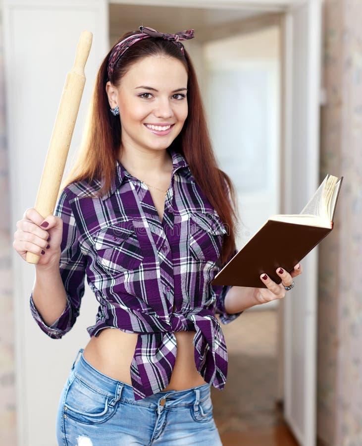 Hübsche Hausfrau liest Kochbuch stockfotografie