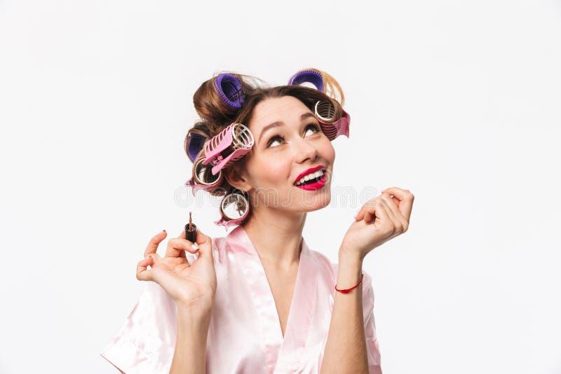 Hübsche Hausfrau mit Lockenwicklern in tragender Robe des Haares lizenzfreie stockbilder