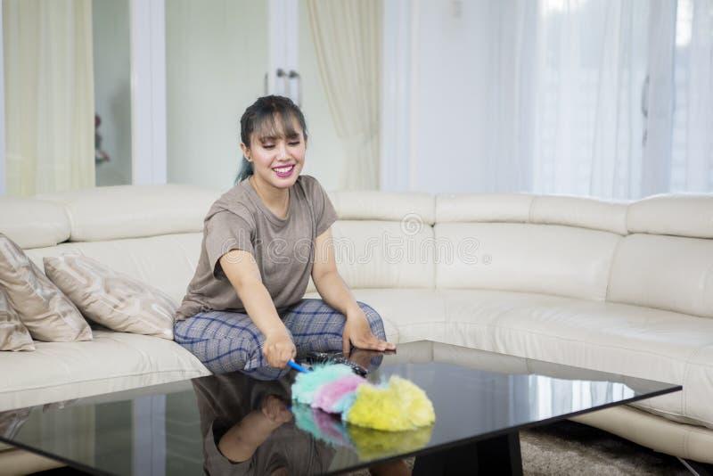 Hübsche Hausfrau säubert Tabelle mit einer Staubtuchbürste lizenzfreie stockfotografie