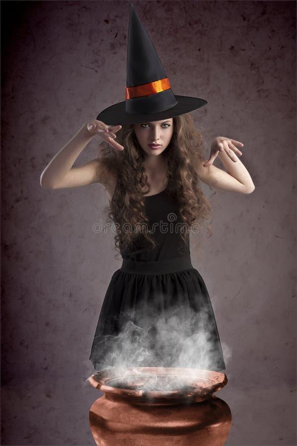 Hübsche Hexe, die etwas Banne bildet lizenzfreies stockbild