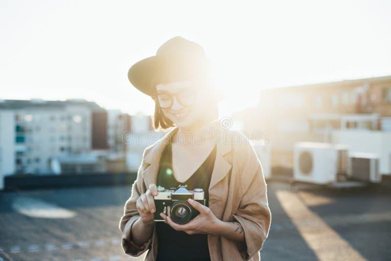 Hübsche Hippie-Frau hält Weinlesekamera stockfoto