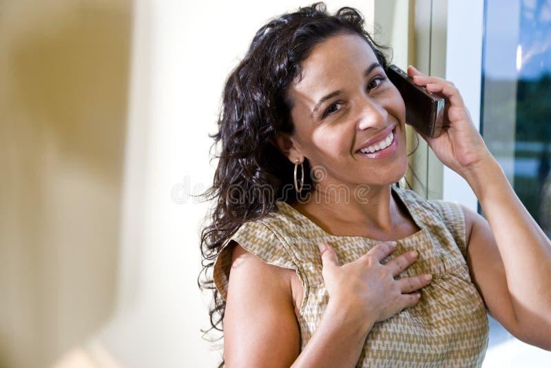 Hübsche hispanische Frau, die auf einem Handy spricht lizenzfreie stockbilder