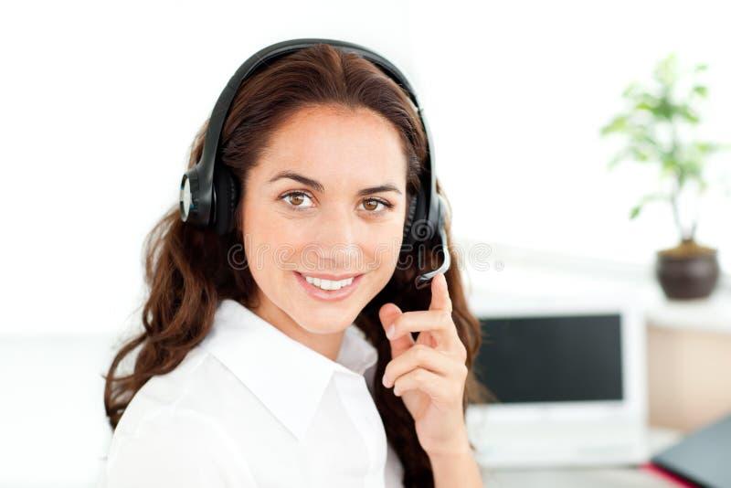 Hübsche hispanische Geschäftsfrau mit Kopfhörersitzen lizenzfreie stockfotos