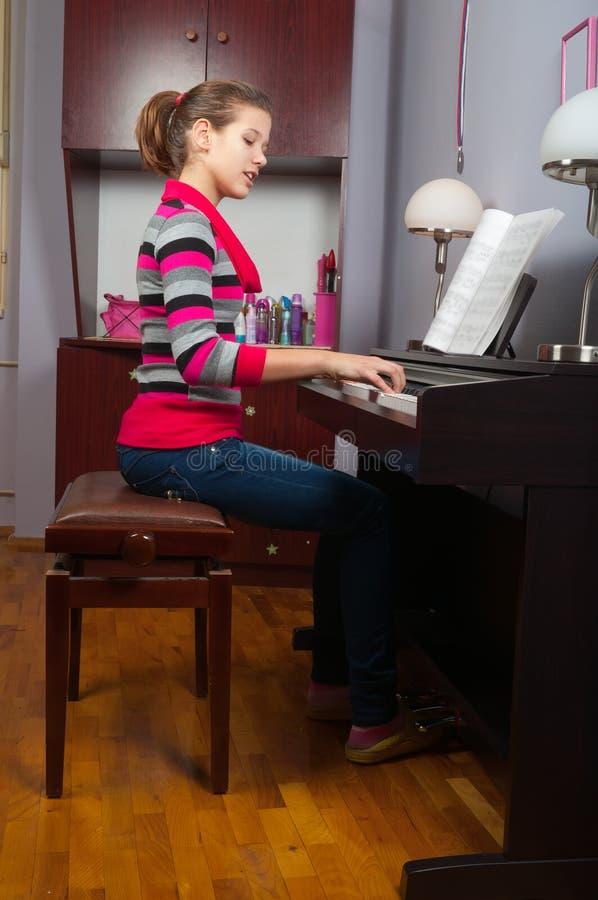 Hübsche Jugendliche, die auf Klavier spielt stockfotos