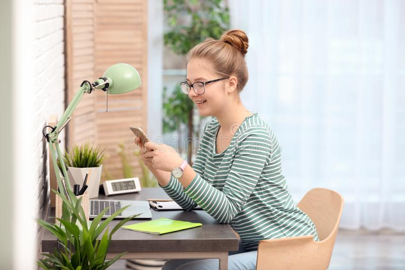 Hübsche Jugendliche, die bei Tisch Handy verwendet lizenzfreies stockbild