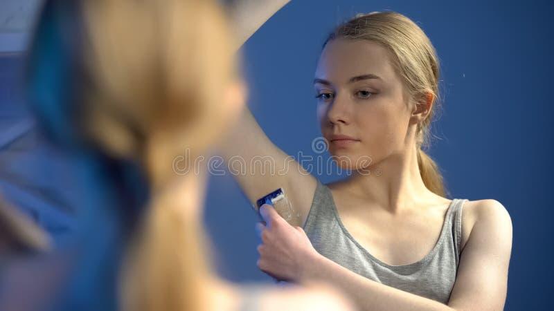 Hübsche jugendliche weibliche Rasierachselhöhle vor Spiegel, Schönheit der persönlichen Hygiene lizenzfreies stockbild