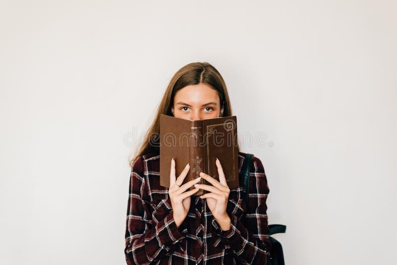 Hübsche JugendlichStudentin mit Buch in ihren Händen, die Gesicht mit Kopienraum- und -WEISShintergrund verstecken lizenzfreie stockfotografie