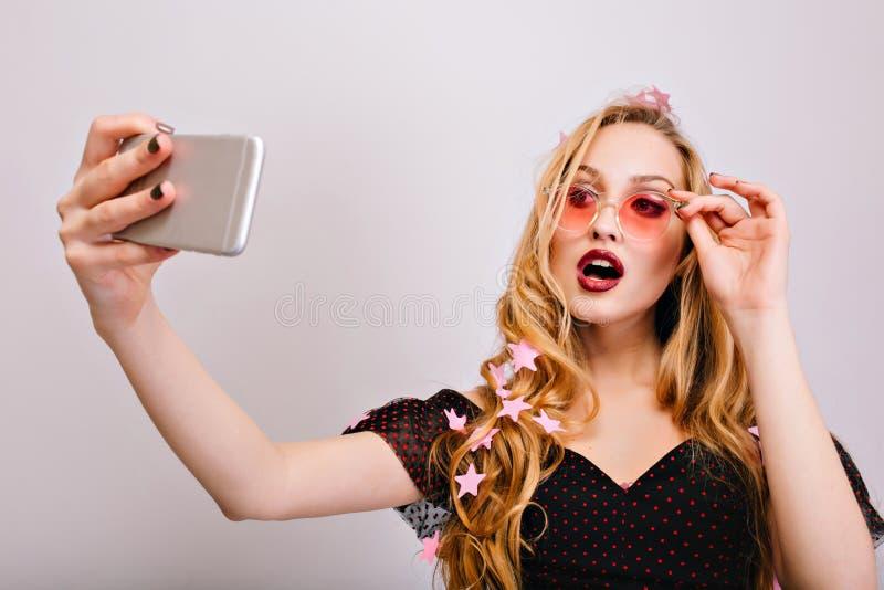 Hübsche junge Blondine, die selfie an der Partei, sexy Blick mit geöffnetem Mund machend nehmen Tragende rosa stilvolle Gl?ser lizenzfreie stockfotografie
