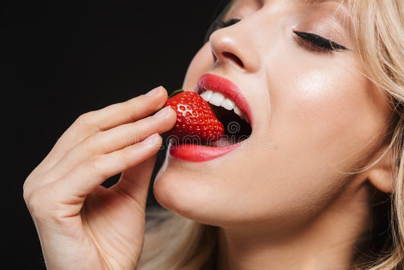 Hübsche junge Blondine mit der roten Aufstellung des hellen Makes-up Lippenlokalisiert über schwarzem Wandhintergrund, Erdbeere z lizenzfreie stockbilder