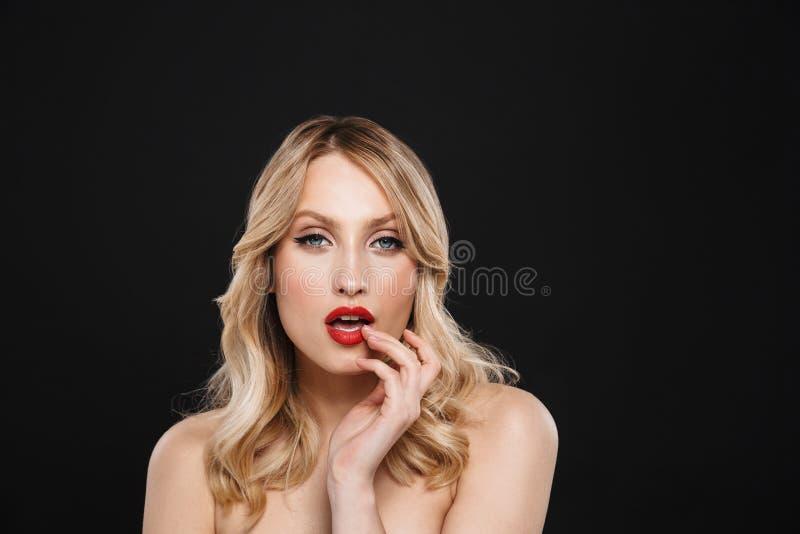 Hübsche junge Blondine mit der roten Aufstellung des hellen Makes-up Lippenlokalisiert über schwarzem Wandhintergrund stockbild