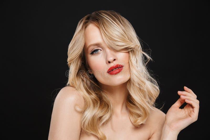 Hübsche junge Blondine mit der roten Aufstellung des hellen Makes-up Lippenlokalisiert über schwarzem Wandhintergrund stockfotos