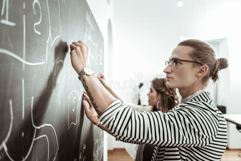 Hübsche junge Damenschneiderin in den Brillen und Skizzen einer schöne Modellzeichnung auf einem Brett stockbild