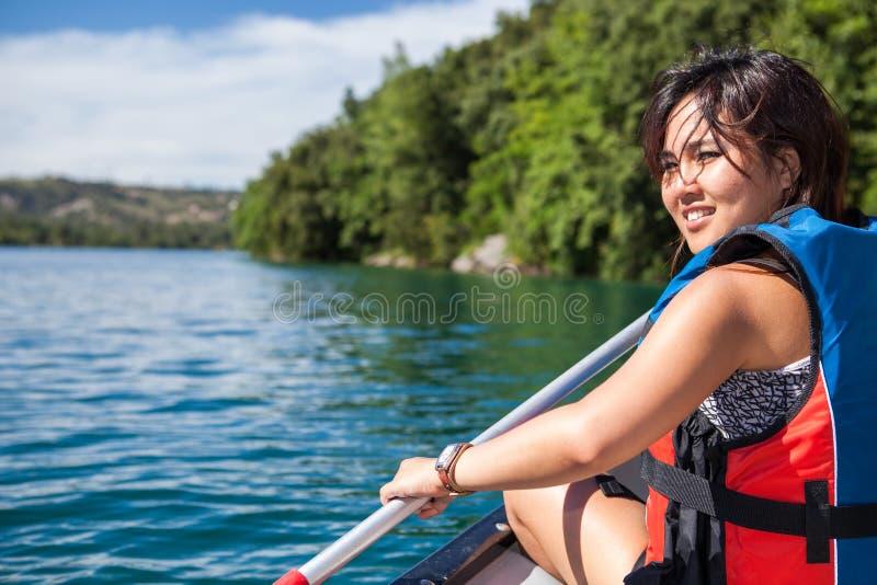 Hübsche, junge Frau auf einem Kanu auf einem See, schaufelnd lizenzfreies stockbild