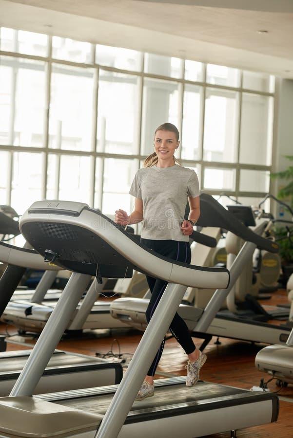 Hübsche junge Frau auf Tretmühle am Fitness-Club lizenzfreies stockfoto