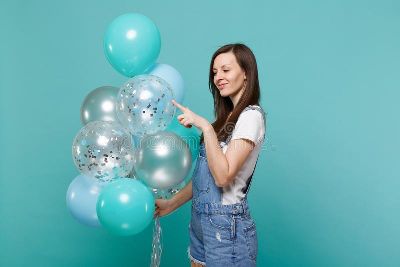 Hübsche junge Frau in der Denimkleidung Zeigefinger auf den bunten Luftballonen feiernd, halten und zeigend an lokalisiert stockfotos