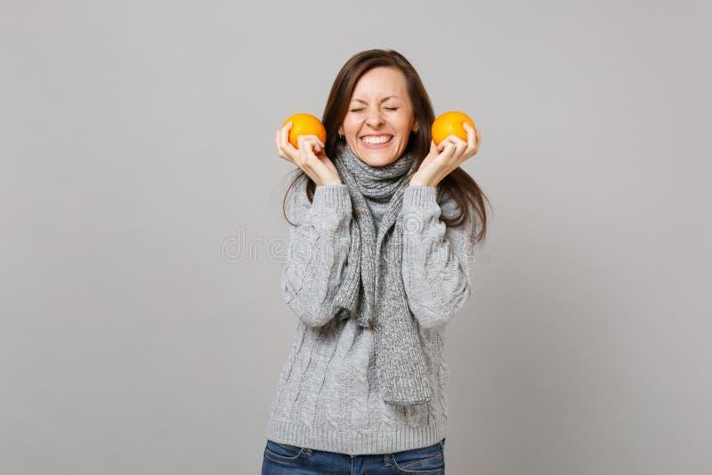 Hübsche junge Frau in der grauen Strickjacke, Schal mit den geschlossenen Augen, die Orangen lokalisiert auf grauem Wandhintergru lizenzfreies stockbild