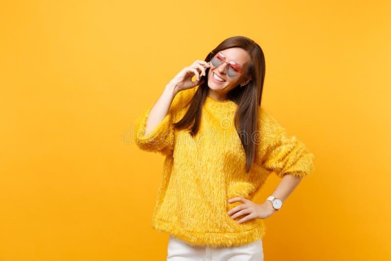 Hübsche junge Frau in der Pelzstrickjacke, Herzgläser sprechend am Handy, angenehmes Leitgespräch an lokalisiert stockbilder