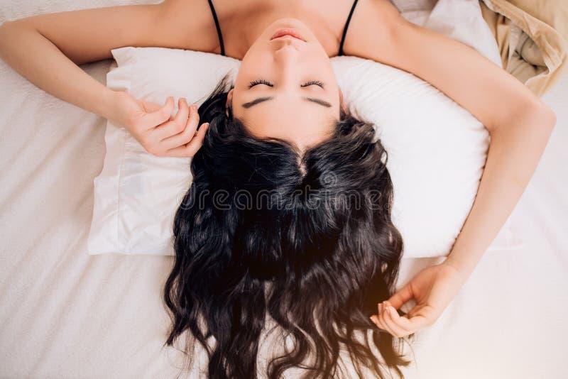 Hübsche junge Frau des Porträts auf Bett lizenzfreie stockfotografie