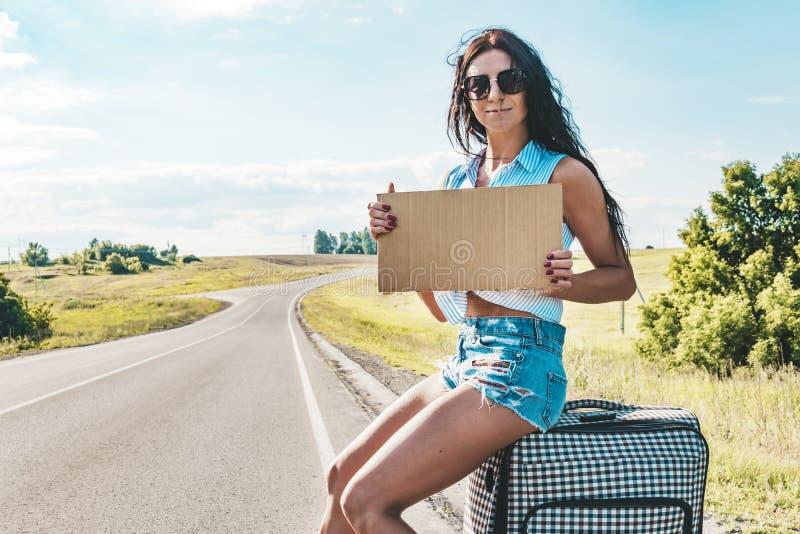 Hübsche junge Frau, die entlang einer Straße per Anhalter fährt und auf eine Landstraße mit ihrem Koffer und leeren Pappplatte wa lizenzfreie stockbilder