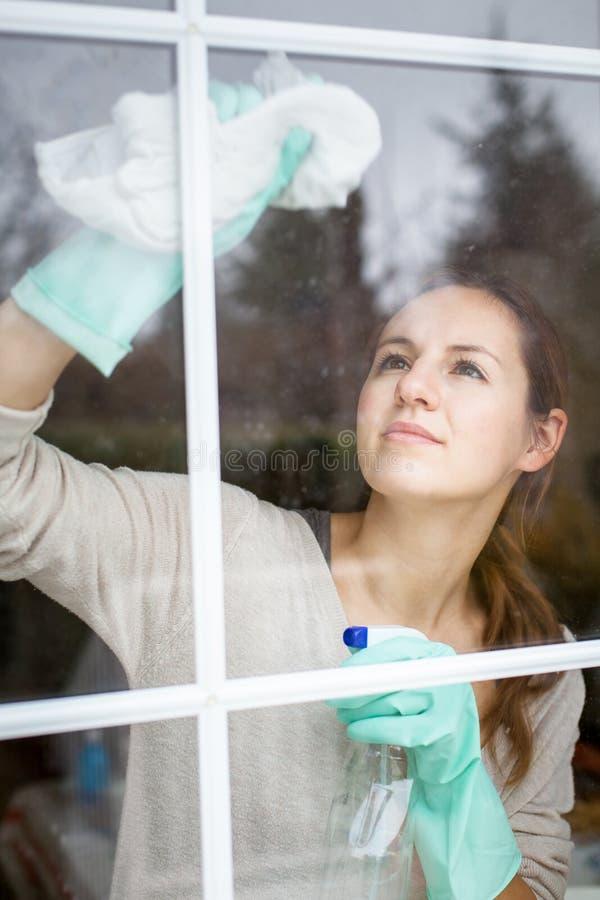 Hübsche, junge Frau, die Hausarbeit - waschende Fenster erledigt lizenzfreie stockbilder