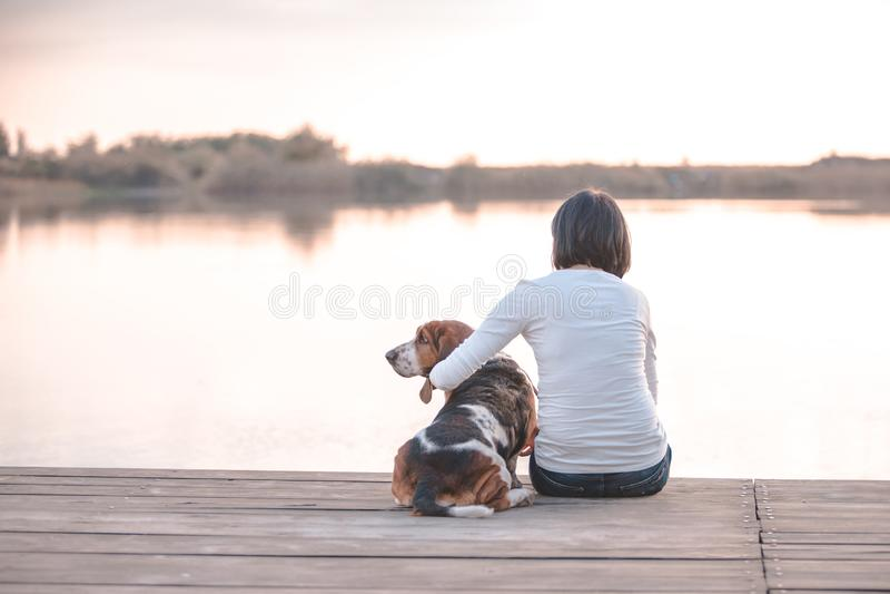 Hübsche junge Frau, die ihren Hund Basset Hound auf dem hölzernen Dock auf dem Fluss umarmt lizenzfreie stockbilder
