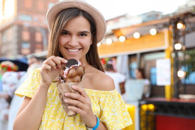 Hübsche junge Frau, die köstliche süße Blasenwaffel mit Eiscreme hält lizenzfreies stockfoto