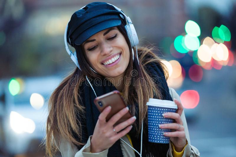 Hübsche junge Frau, die Musik mit Handy beim Trinken des Kaffees in der Straße nachts hört lizenzfreie stockfotos