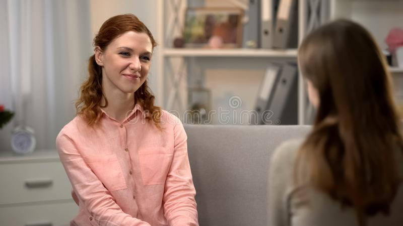 Hübsche junge Frau, die zur Freundin, sprechend auf Sofa, Gesellschaft lächelt lizenzfreies stockfoto
