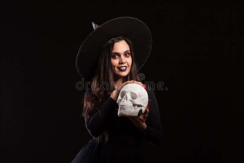 Hübsche junge Frau in einem Hexenkostüm für Halloween-Partei, die schlechte Hexerei tut lizenzfreies stockbild