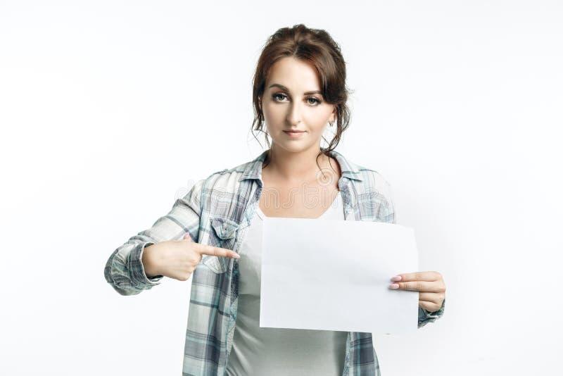 Hübsche junge Frau in einem weißen Hemd und in einem hellblauen karierten Hemd hält ein leeres Blatt in ihren Händen, stockfotografie