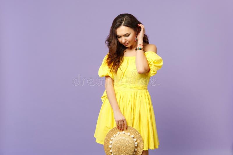 Hübsche junge Frau im gelben Kleid, das den Sommerhut, schauend hinunter das Halten der Hand auf Haar auf Pastellveilchen hält stockfoto