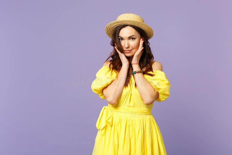 Hübsche junge Frau im gelben Kleid, Sommerhut setzte Hand sützen auf dem Kinn und schaute Kamera auf Pastellveilchen stockfoto