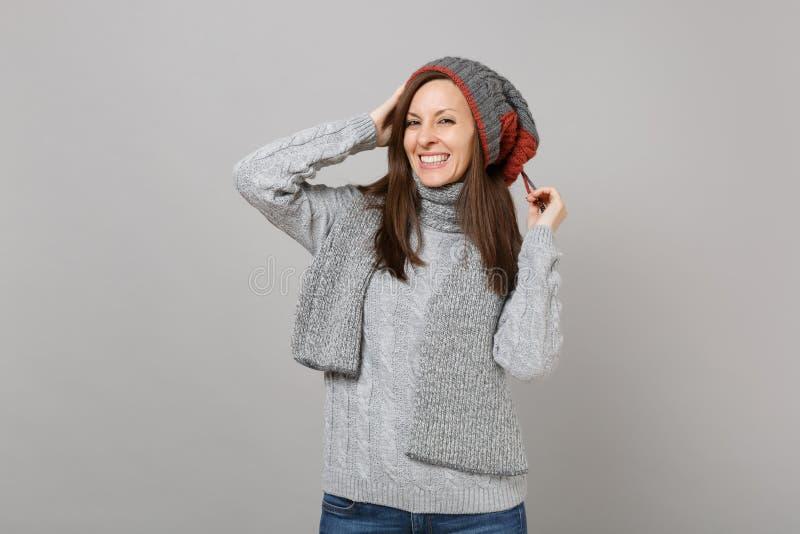 Hübsche junge Frau im grauen Strickjackenhut und -schal, die Hände auf den Kopf lokalisiert auf grauem Hintergrund in Studio eins stockfotografie