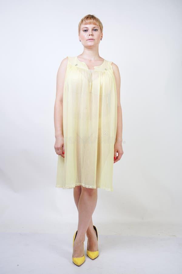 Hübsche junge Frau mit dem kurzen Haar und molliger Körper, der transparentes Nachthemd trägt und auf weißem Studiohintergrund al lizenzfreie stockfotos