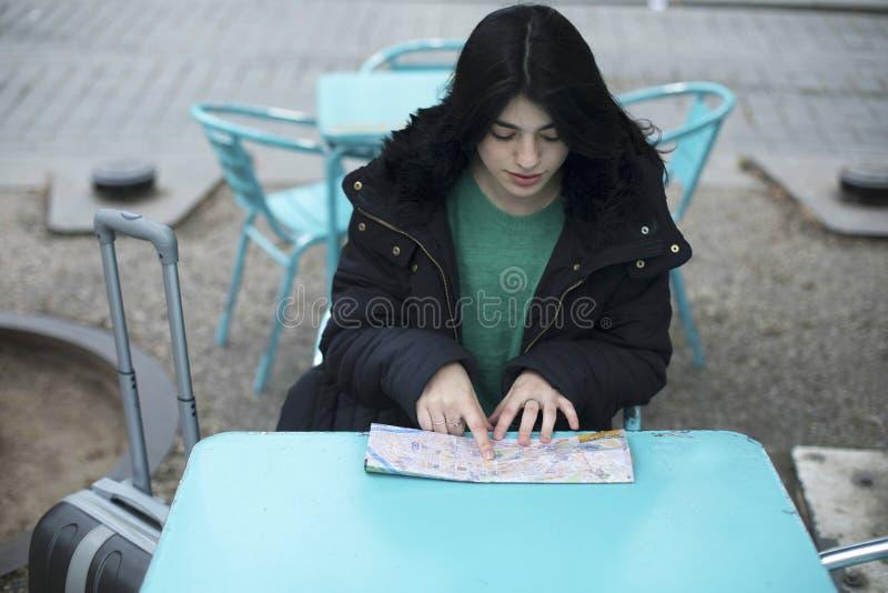 Hübsche junge Frau mit der Karte, die bei Tisch am alten Stadtcafé, draußen sitzt lizenzfreies stockfoto