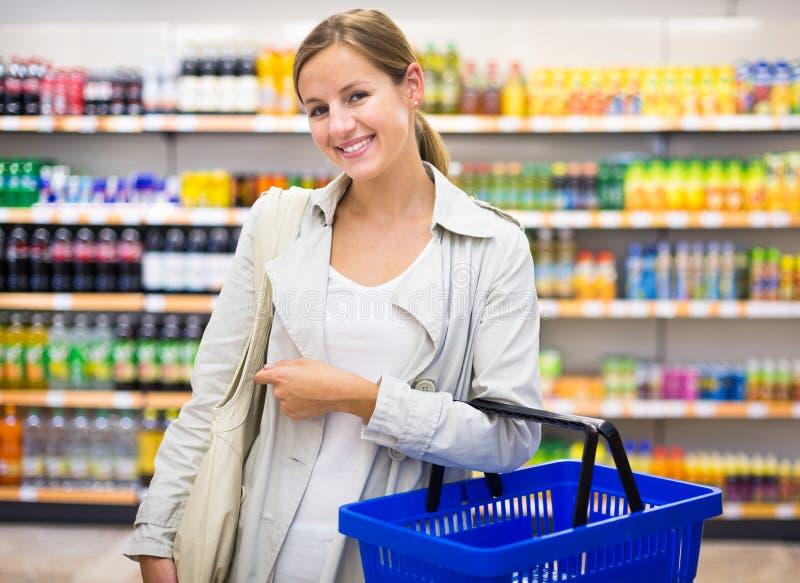 Hübsche, junge Frau mit kaufenden Lebensmittelgeschäften eines Einkaufskorbs stockbilder