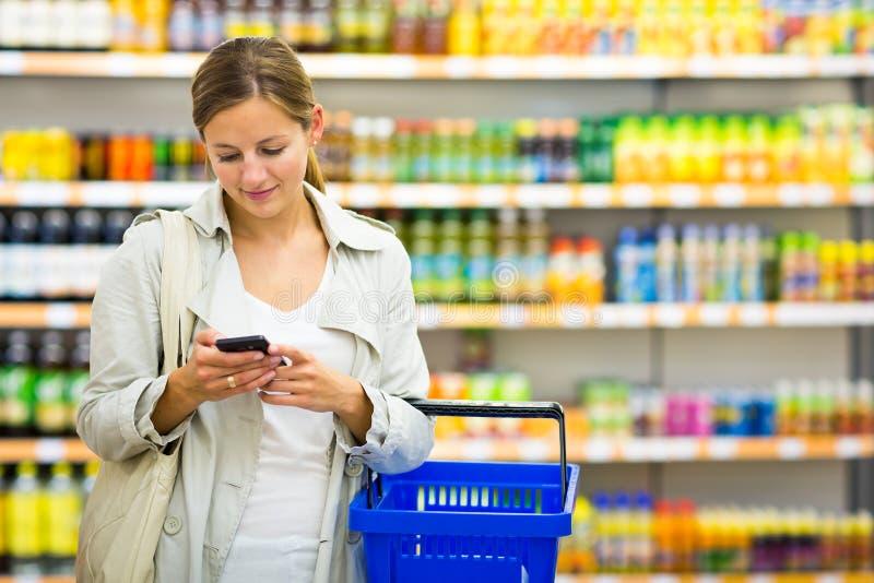 Hübsche, junge Frau mit kaufenden Lebensmittelgeschäften eines Einkaufskorbs stockfotografie