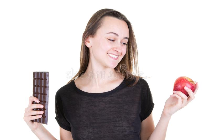Hübsche junge Frau mit rotem Apfel und der Schokoriegel, der gereizt wird, versuchen, gesund zu sein lizenzfreie stockbilder
