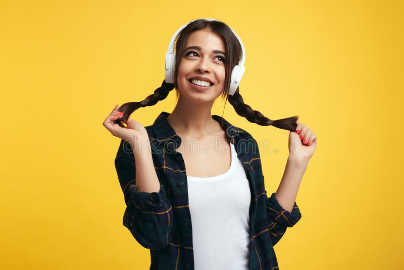 Hübsche junge Frau mit weißen Kopfhörern, hört Musik und fühlt sich froh und spielt mit ihren Pferdeschwänzen und weg schaut mit  stockbild
