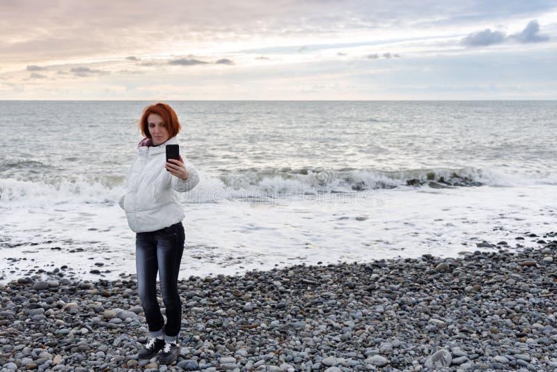 Hübsche junge Frau steht auf der Küste am Frühling gegen den Sonnenuntergang und nimmt ein selfie stockbild