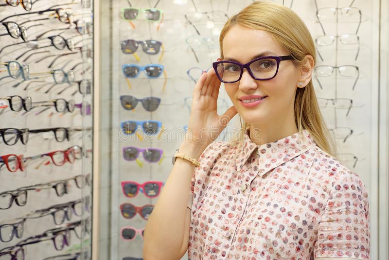 Hübsche junge Frau wählt Gläser im Optikerspeicher stockfoto