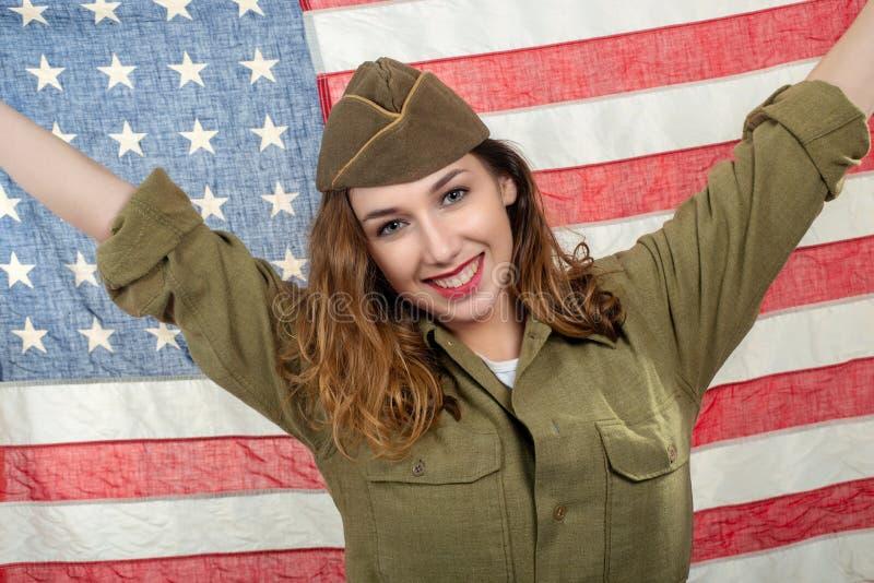 Hübsche junge Frau in wwii Uniform wir mit einer amerikanischen Flagge lizenzfreie stockbilder
