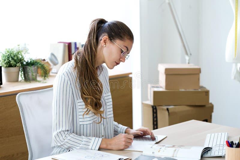 Hübsche junge Geschäftsfrau, die Anmerkungen in ihr Notizbuch im Büro schreibt lizenzfreies stockfoto