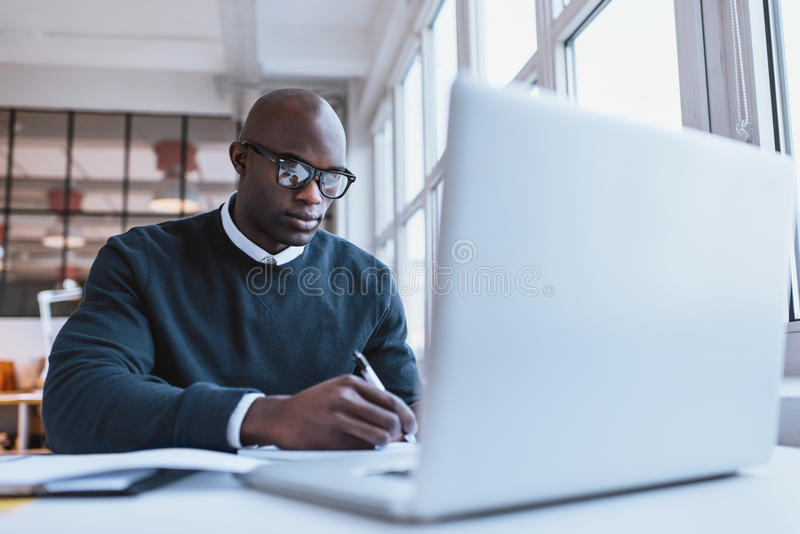 Hübsche junge Geschäftsmannschreibensanmerkungen stockbilder