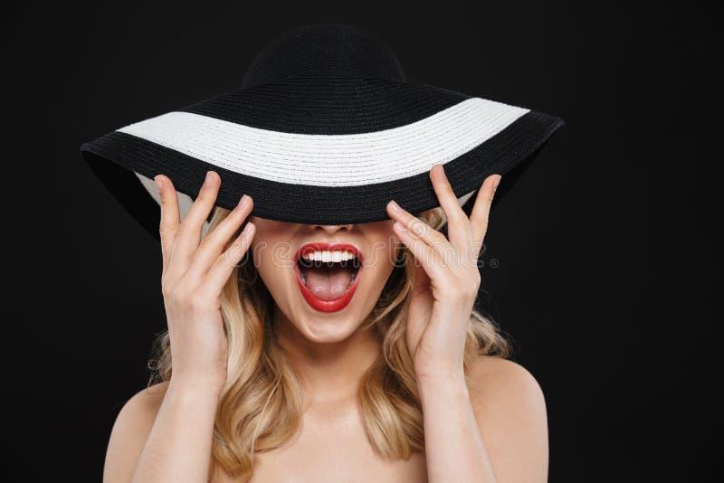 Hübsche junge glückliche Blondine mit der roten Aufstellung des hellen Makes-up Lippenlokalisiert über tragendem Hut des schwarze stockbilder
