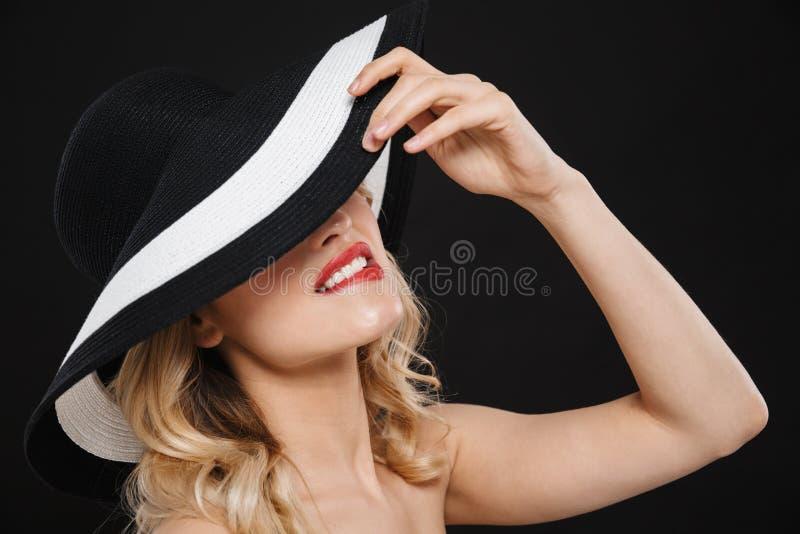 Hübsche junge glückliche nette Blondine mit der roten Aufstellung des hellen Makes-up Lippenlokalisiert über tragendem Hut des sc stockbild