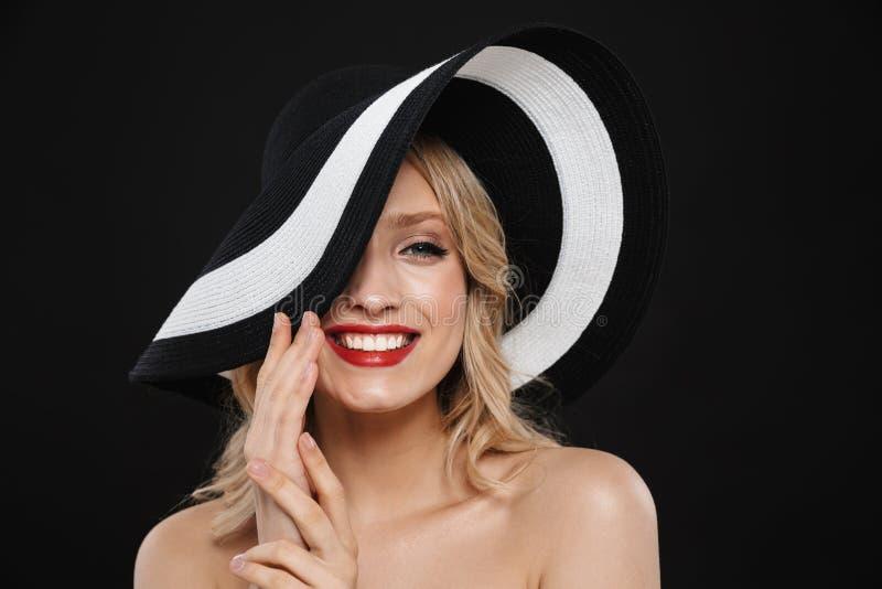Hübsche junge glückliche nette Blondine mit der roten Aufstellung des hellen Makes-up Lippenlokalisiert über tragendem Hut des sc lizenzfreie stockbilder